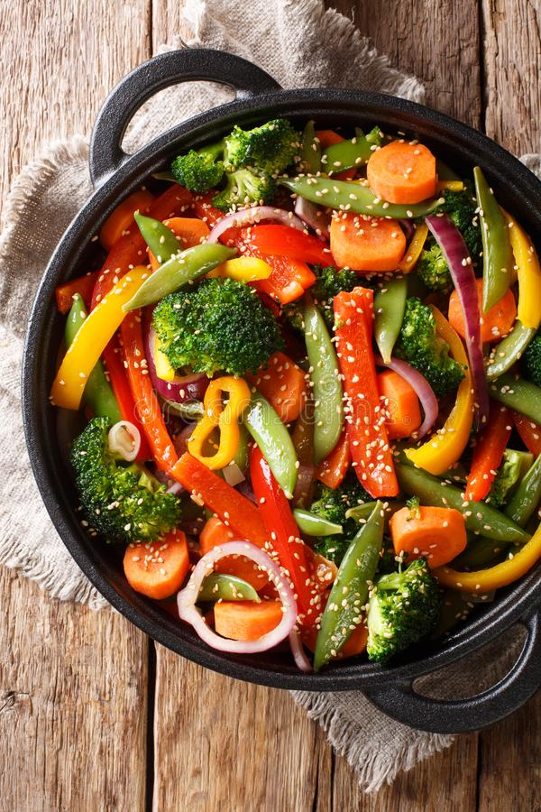 Ανακατώστε τα τηγανητά των λαχανικών με την κινηματογράφηση σε πρώτο πλάνο σουσαμιού σε ένα κύπελλο στον πίνακα, αγροτικά Κάθετη  στοκ φωτογραφία με δικαίωμα ελεύθερης χρήσης