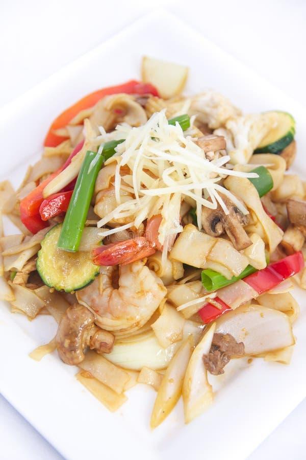 Ανακατώστε τα τηγανισμένα επίπεδα νουντλς ρυζιού με τη σάλτσα πιπεροριζών. στοκ φωτογραφίες