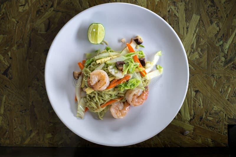 Ανακατώστε τα τηγανισμένα νουντλς με τις γαρίδες, το λάχανο, το καρότο, το καλαμπόκι και το μανιτάρι στο άσπρο πιάτο στον ξύλινο  στοκ εικόνα με δικαίωμα ελεύθερης χρήσης