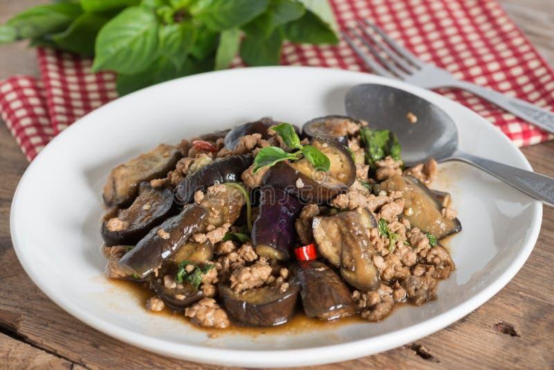 Ανακατώστε την τηγανισμένη μελιτζάνα με το κομματιασμένο χοιρινό κρέας και το βασιλικό στο άσπρο πιάτο στοκ εικόνες