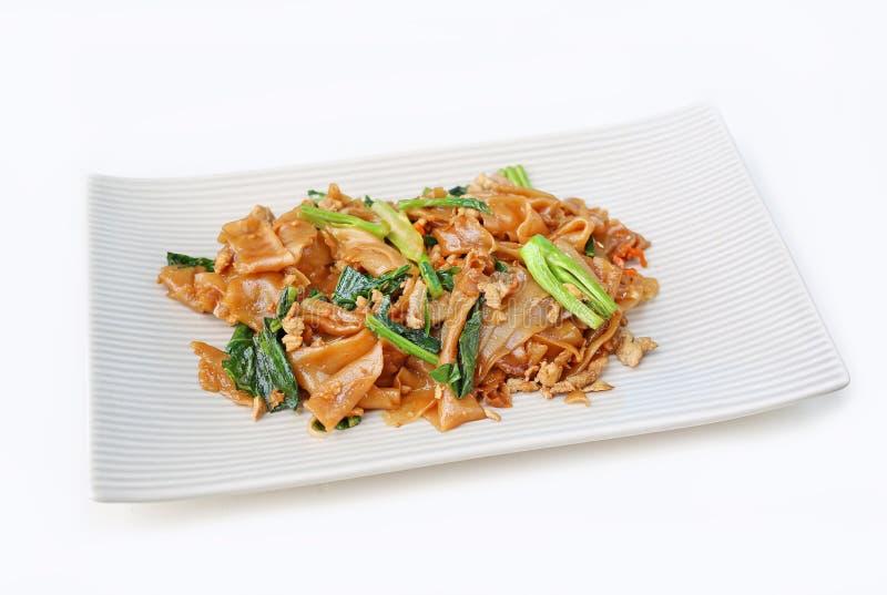 Ανακατώστε το τηγανισμένα επίπεδα νουντλς και το χοιρινό κρέας με τη σκοτεινή σάλτσα σόγιας στοκ εικόνες