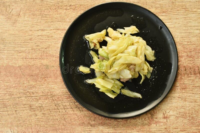 Ανακατώστε το τηγανισμένα λάχανο και το χοιρινό κρέας φετών με τη σάλτσα ψαριών στο πιάτο στοκ εικόνες