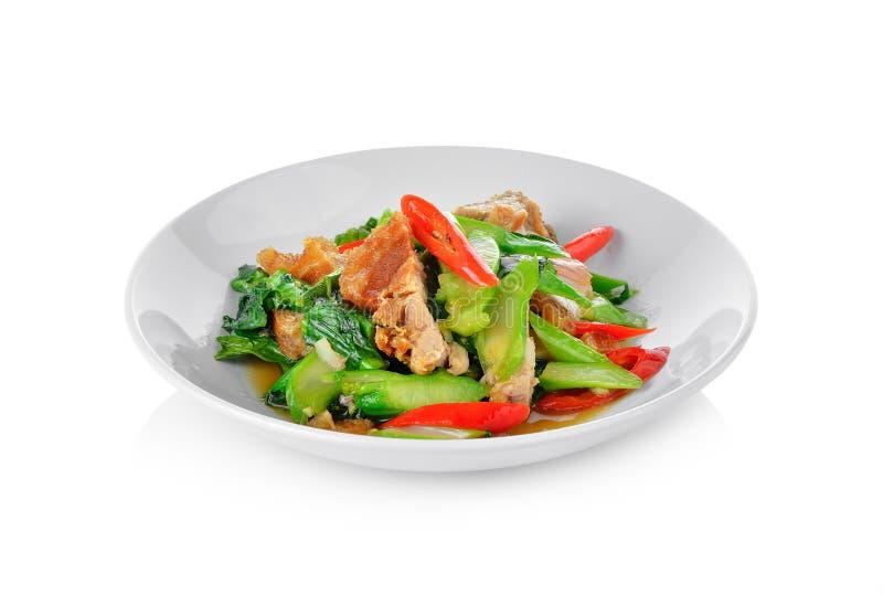 Ανακατώστε το τηγανισμένο κατσαρό λάχανο με το τριζάτο χοιρινό κρέας στο άσπρο πιάτο στοκ φωτογραφία