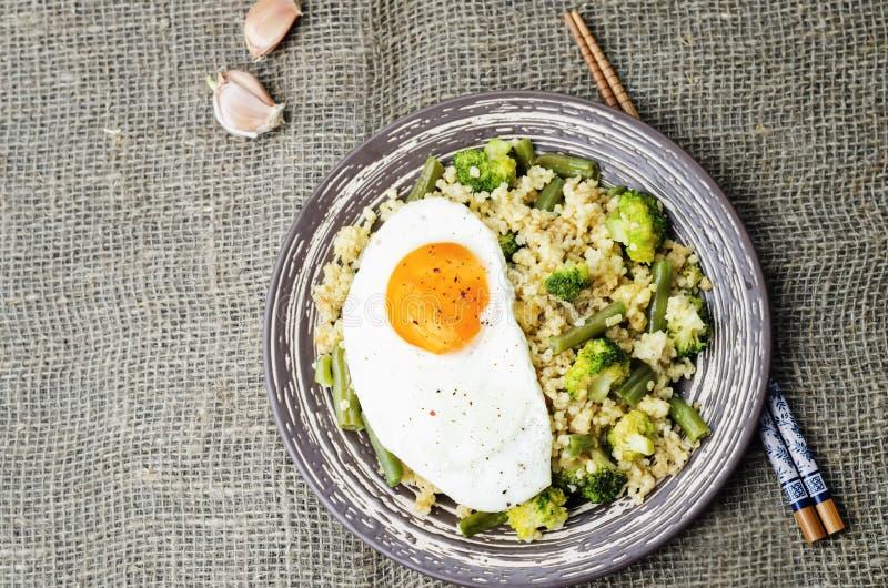 Ανακατώστε το τηγανισμένο κεχρί με το μπρόκολο, τα πράσινα φασόλια και το τηγανισμένο αυγό στοκ εικόνα