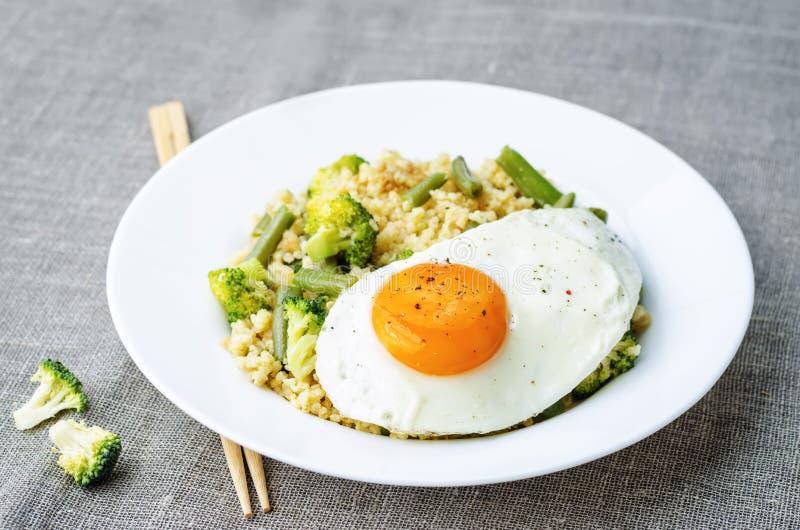 Ανακατώστε το τηγανισμένο κεχρί με το μπρόκολο, τα πράσινα φασόλια και το τηγανισμένο αυγό στοκ φωτογραφία με δικαίωμα ελεύθερης χρήσης