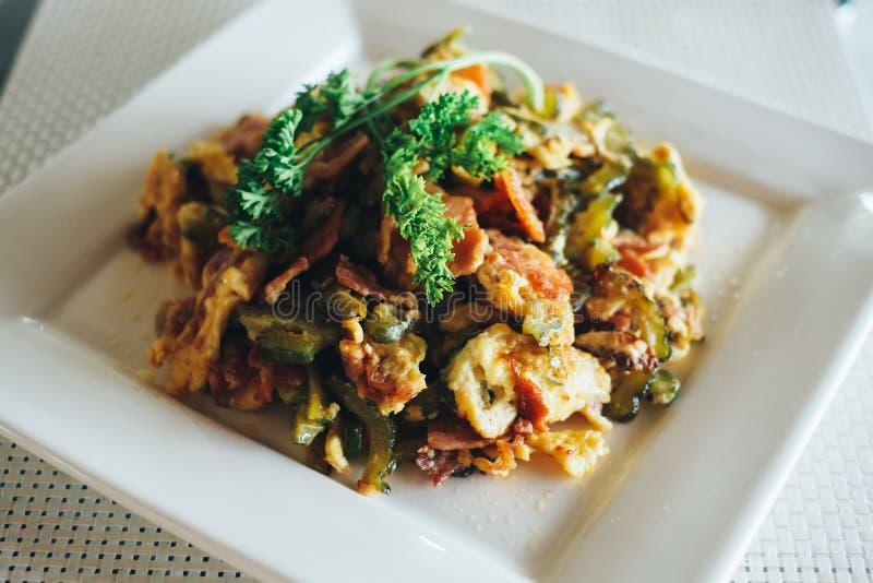 Ανακατώστε το τηγανισμένο πικρό πεπόνι με τα αυγά και το μπέϊκον στοκ εικόνες