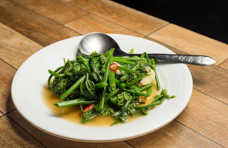 Ανακατώστε το τηγανισμένο σπανάκι νερού ή τα βιετναμέζικα τηγάνισαν τη δόξα πρωινού, toi xao rau muong στο άσπρο πιάτο στον ξύλιν στοκ φωτογραφία