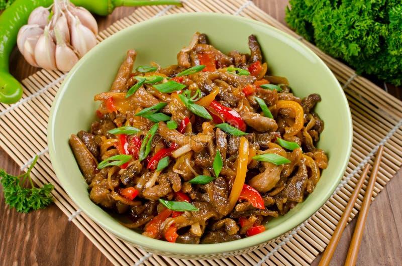 Ανακατώστε το χοιρινό κρέας τηγανητών, τα γλυκά πιπέρια, τα κρεμμύδια και το σκόρδο στοκ φωτογραφίες με δικαίωμα ελεύθερης χρήσης
