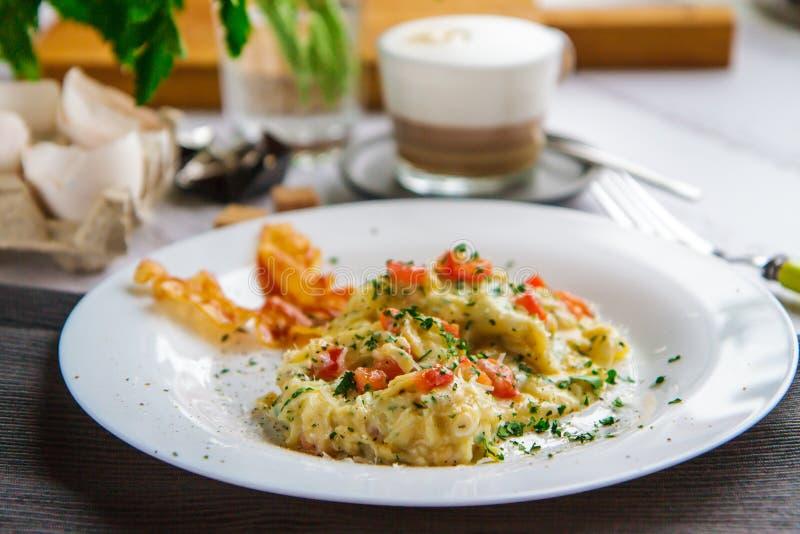 Ανακατώστε των αυγών και του μπέϊκον σε μια άσπρη πλάγια όψη πιάτων στοκ φωτογραφία