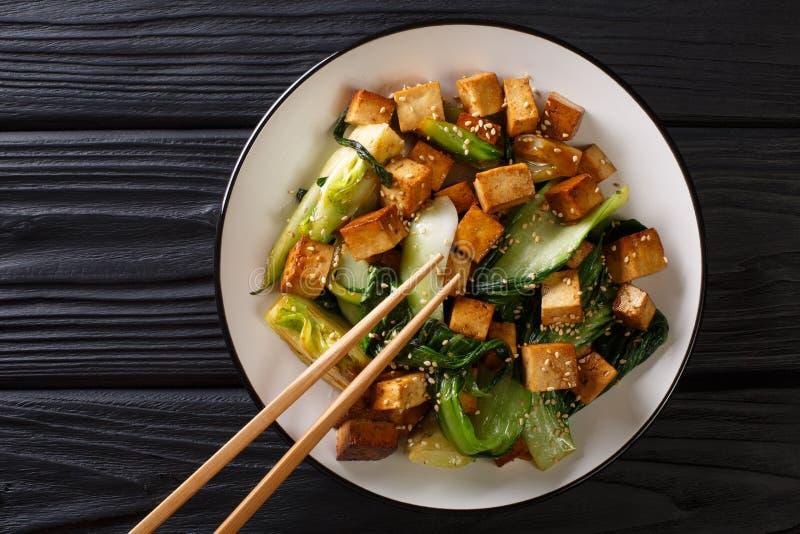 Ανακατώστε tofu τηγανητών με το bok choy και την κινηματογράφηση σε πρώτο πλάνο σπόρων σουσαμιού σε ένα πιάτο οριζόντια τοπ άποψη στοκ εικόνα