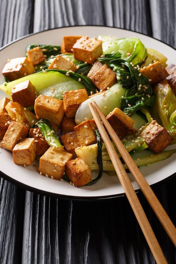 Ανακατώστε tofu τηγανητών με το bok choy και την κινηματογράφηση σε πρώτο πλάνο σπόρων σουσαμιού σε ένα πιάτο κάθετος στοκ φωτογραφίες με δικαίωμα ελεύθερης χρήσης
