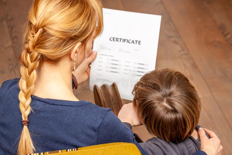 Ανακουφίζοντας γιος μητέρων παρά το κακό σχολικό πιστοποιητικό στοκ φωτογραφίες με δικαίωμα ελεύθερης χρήσης