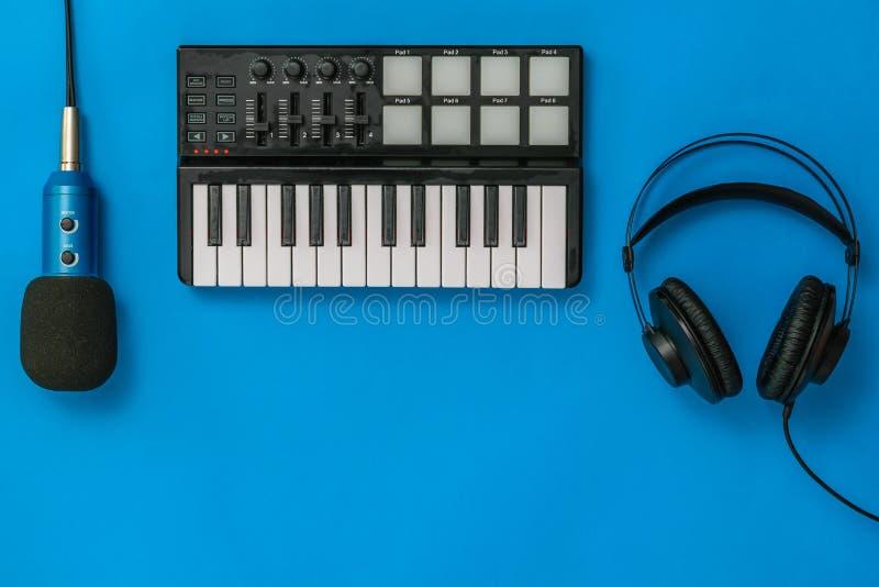 Αναμίκτης, μικρόφωνο και ακουστικά μουσικής στο μπλε υπόβαθρο Η έννοια της οργάνωσης εργασιακών χώρων στοκ εικόνες