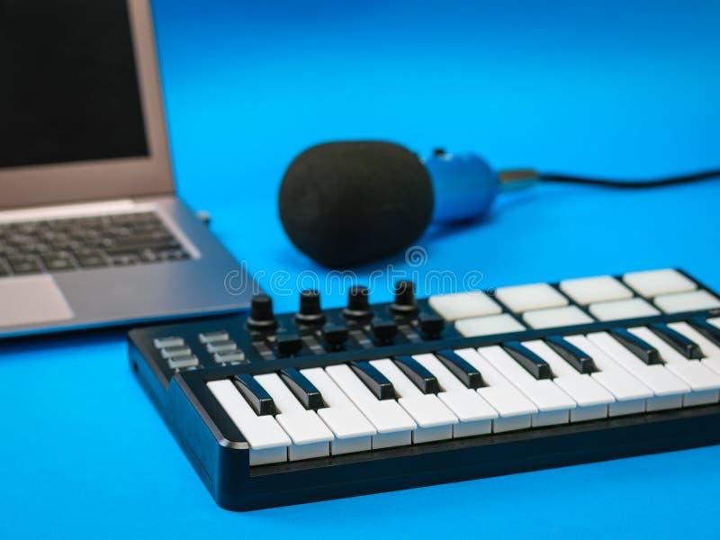 Αναμίκτης μουσικής, ανοικτά lap-top και μικρόφωνο με τα καλώδια στο μπλε υπόβαθρο στοκ εικόνα με δικαίωμα ελεύθερης χρήσης