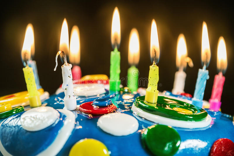 Αναμμένα κεριά σε ένα κέικ γενεθλίων στοκ φωτογραφία