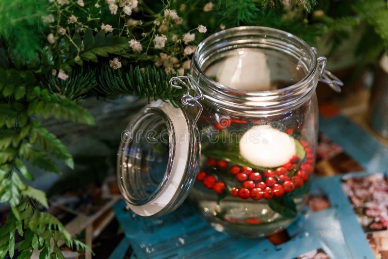 Αναμμένο κερί στο βάζο γυαλιού με τα άσπρα λουλούδια και τα πράσινα φύλλα στοκ εικόνα