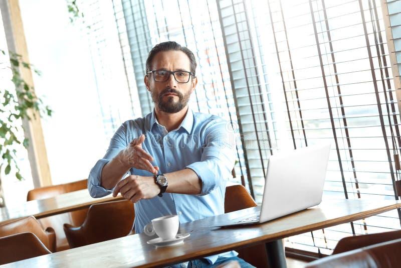 Αναμονή τη διαταγή Έμπορος στα γυαλιά που κάθεται στον καφέ με το lap-top και τον καφέ που δείχνει στο ρολόι σχετικό στοκ φωτογραφίες με δικαίωμα ελεύθερης χρήσης
