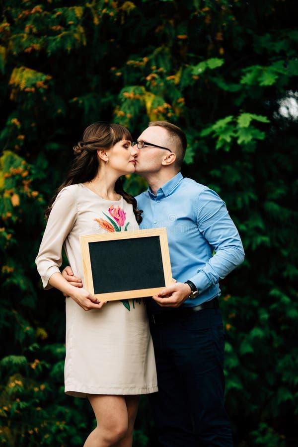 Αναμονή του έγκυου ευτυχούς μοντέρνου ζεύγους που κρατά έναν κενό πίνακα ξυλάνθρακα στοκ εικόνες με δικαίωμα ελεύθερης χρήσης