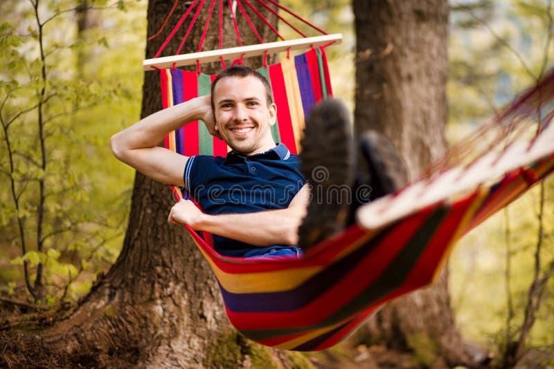 Αναπαυτικός νεαρός άνδρας που καθορίζει στην αιώρα στη μέση του δάσους στο πάρκο Έννοια να ονειρευτεί, της ευημερίας και των υγιώ στοκ φωτογραφίες με δικαίωμα ελεύθερης χρήσης