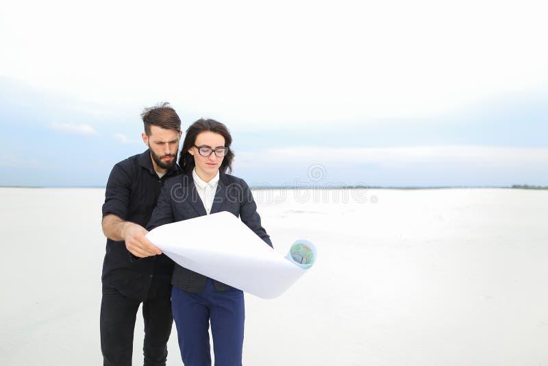 Αναπληρωτής θηλυκό και αρσενικό αρχιτεκτόνων με τη whatman συζήτηση εγγράφου στοκ εικόνες