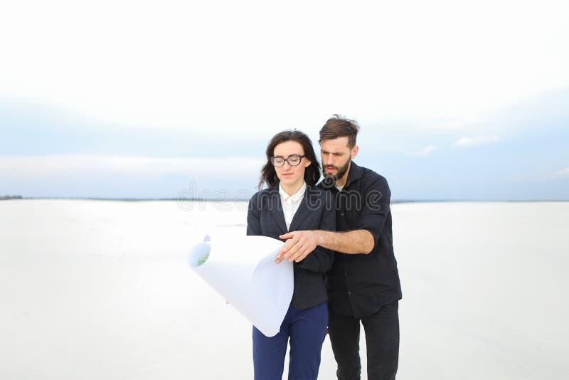 Αναπληρωτής θηλυκό και αρσενικό αρχιτεκτόνων με τη whatman συζήτηση εγγράφου στοκ φωτογραφία με δικαίωμα ελεύθερης χρήσης