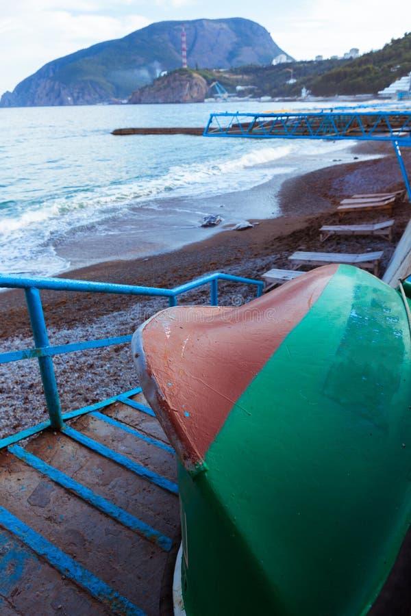 Αναποδογυρισμένη πράσινη ξύλινη βάρκα σε μια σκάλα πετρών κοντά στη θάλασσα στοκ φωτογραφία με δικαίωμα ελεύθερης χρήσης