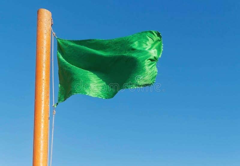 Αναπτύξτε την πράσινη σημαία σε ένα υπόβαθρο του μπλε ουρανού στοκ εικόνες