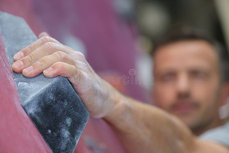 Αναρρίχηση νεαρών άνδρων εσωτερική στον τεχνητό bouldering τοίχο κοντά επάνω στοκ εικόνα