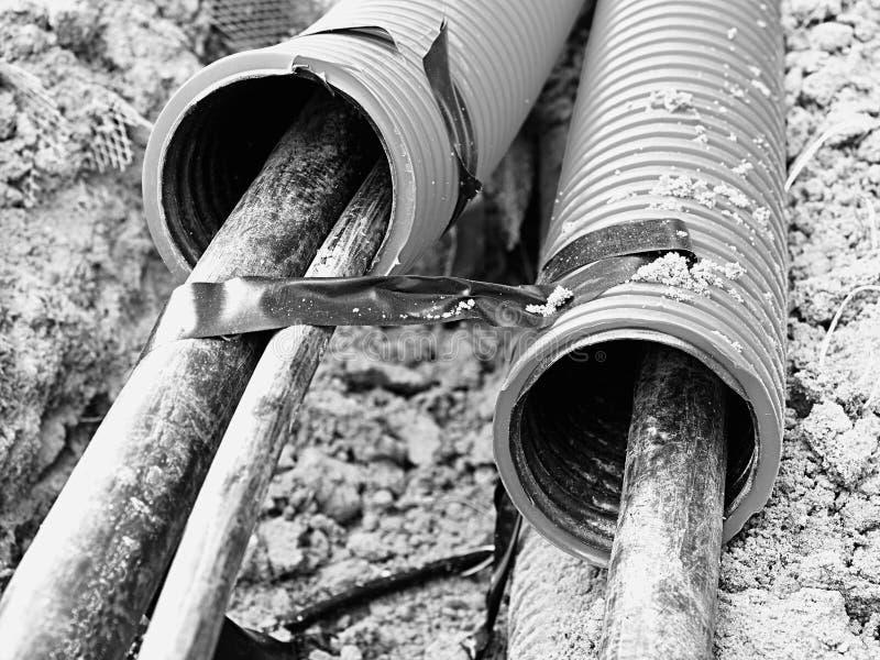 Ανασκαφή της τάφρου με τα μαύρα καλώδια στον προστατευτικό HDPE σωλήνα Γραμμές μεταλλικών και καλωδίων οπτικών ινών στοκ εικόνα