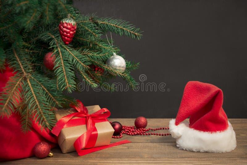 Ανασκόπηση διακοπών Χριστουγέννων Δώρα με μια κόκκινα κορδέλλα, ένα καπέλο Santa ` s και ένα ντεκόρ κάτω από ένα χριστουγεννιάτικ στοκ εικόνα με δικαίωμα ελεύθερης χρήσης