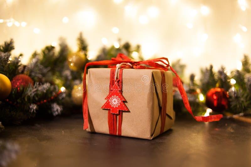Ανασκόπηση διακοπών Χριστουγέννων Δώρα με μια κόκκινα κορδέλλα, ένα Santa ` s ΚΑΠ και ένα ντεκόρ κάτω από ένα χριστουγεννιάτικο δ στοκ εικόνα