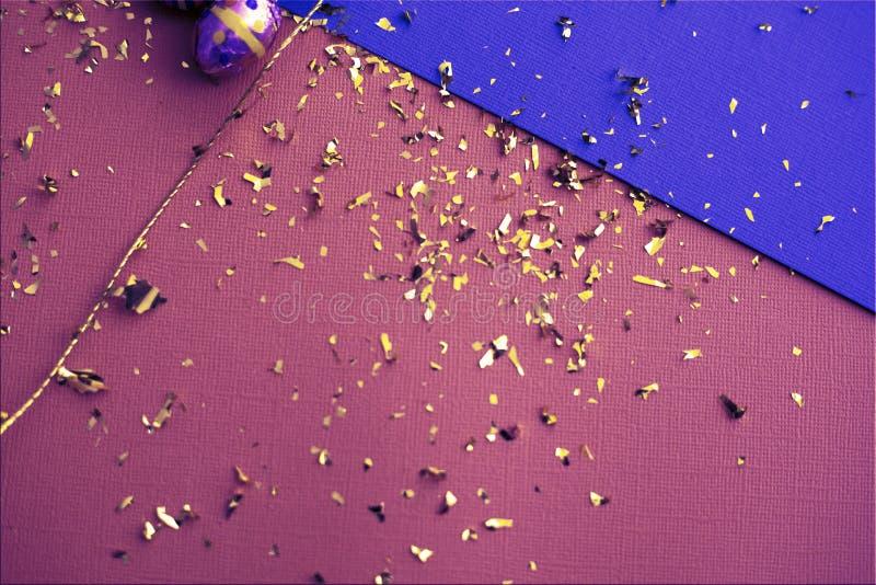 ανασκόπηση ζωηρόχρωμο Πάσχ&al Χρυσό κομφετί στα χρωματισμένα φύλλα Χρυσό αυγό Πάσχας στην επιφάνεια Τοπ άποψη των ρυθμίσεων ντεκό στοκ εικόνες