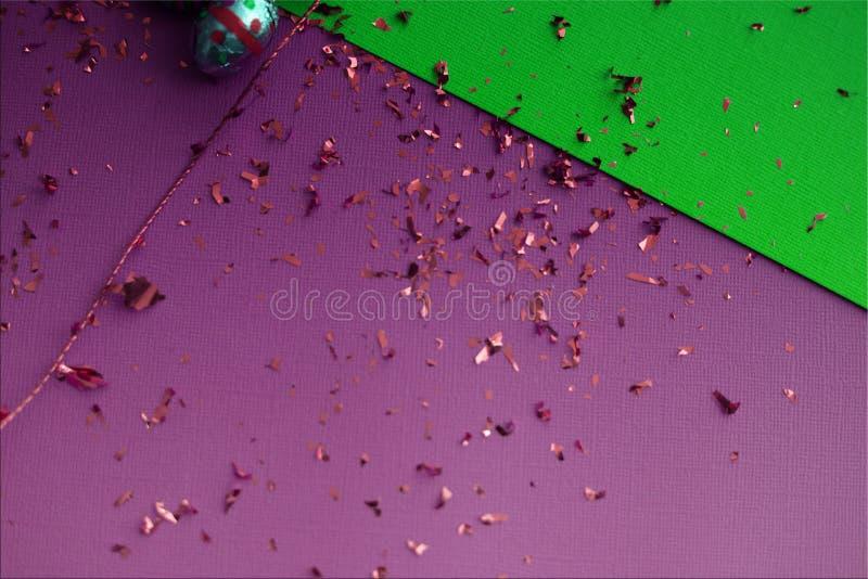 ανασκόπηση ζωηρόχρωμο Πάσχ&al Χρυσό κομφετί στα χρωματισμένα φύλλα Χρυσό αυγό Πάσχας στην επιφάνεια Τοπ άποψη των ρυθμίσεων ντεκό στοκ εικόνες με δικαίωμα ελεύθερης χρήσης