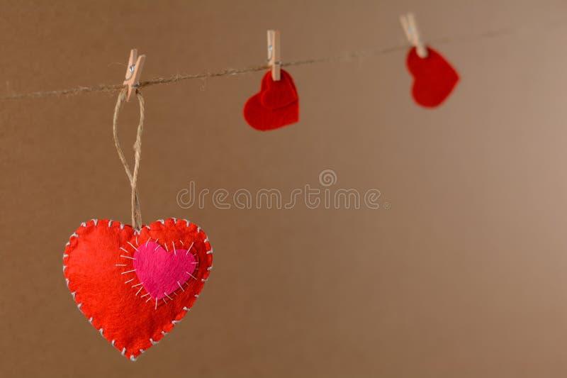 Ανασκόπηση ημέρας βαλεντίνων Καρδιά από αισθητός στο σχοινί με το clothespin στο υπόβαθρο στοκ εικόνα