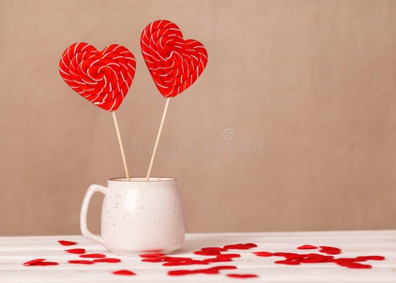 Ανασκόπηση ημέρας βαλεντίνων ` s Δύο καρδιά-διαμορφωμένες καραμέλες σε ένα άσπρο φλυτζάνι, μια διασπορά των μικρών καρδιών σε ένα στοκ φωτογραφία