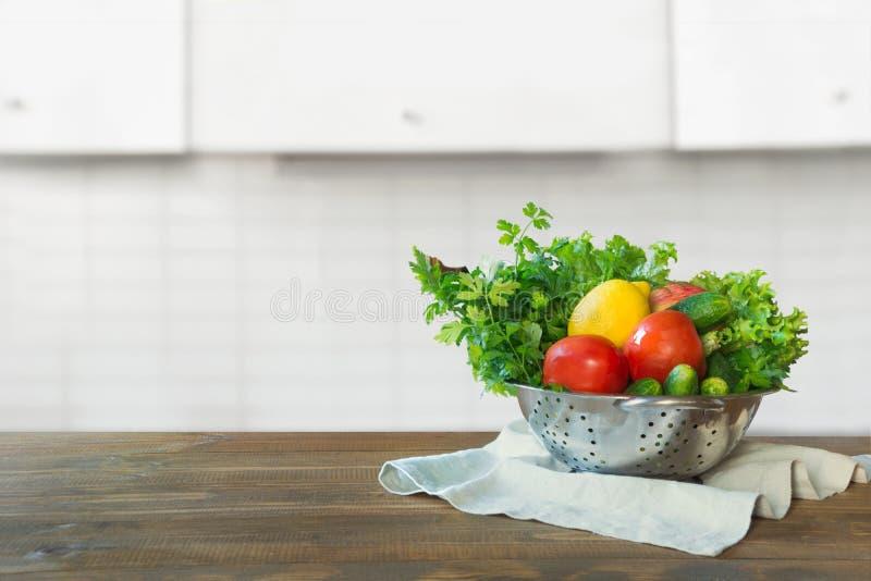 ανασκόπηση που θολώνεται Σύγχρονη κουζίνα με τα φρέσκα λαχανικά ξύλινο tabletop, διάστημα για τα προϊόντα επίδειξης στοκ εικόνα