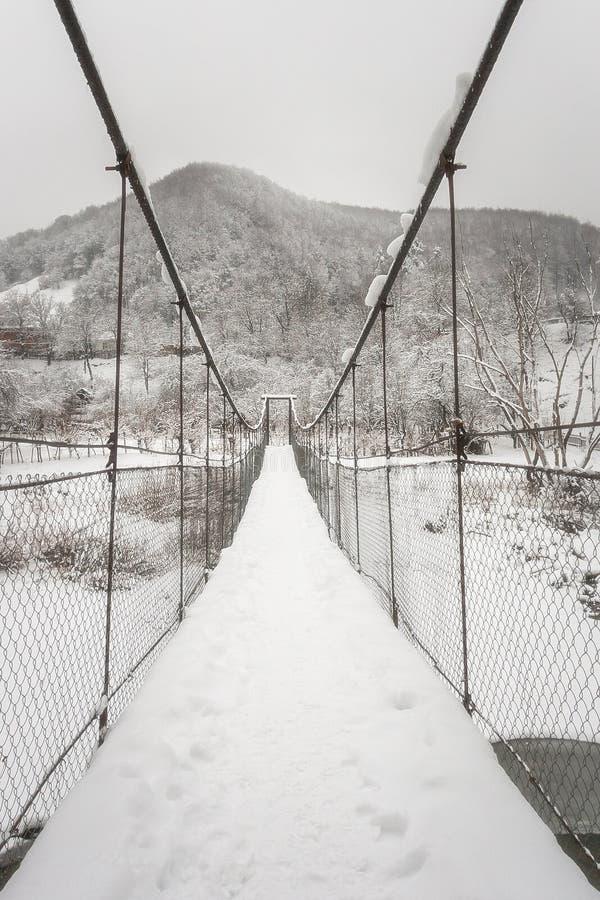 Ανασταλμένη ξύλινη γέφυρα πέρα από έναν ποταμό χειμερινών βουνών στοκ φωτογραφία με δικαίωμα ελεύθερης χρήσης