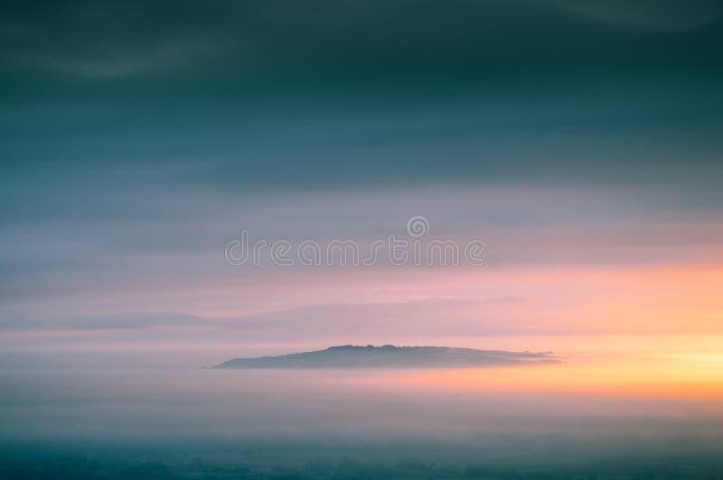 Ανατολή επάνω από ένα υπέροχα misty τοπίο με ακριβώς την κορυφή του Hill Bredon που αυξάνεται από την ομίχλη στοκ φωτογραφία