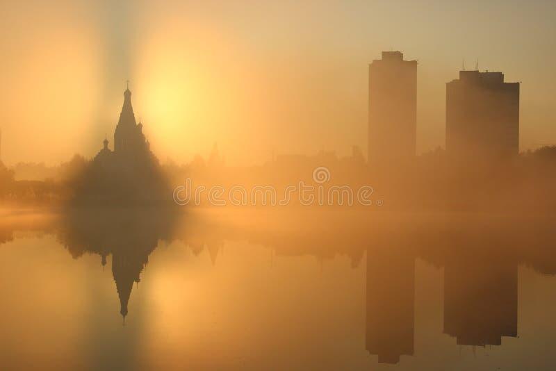 Ανατολή κοντά στην εκκλησία, υπόβαθρο πόλεων ομιχλώδες πρωί Η υδρονέφωση πέρα από το νερό ουρανοξύστες γύρω από το παλαιό κτήριο στοκ φωτογραφίες