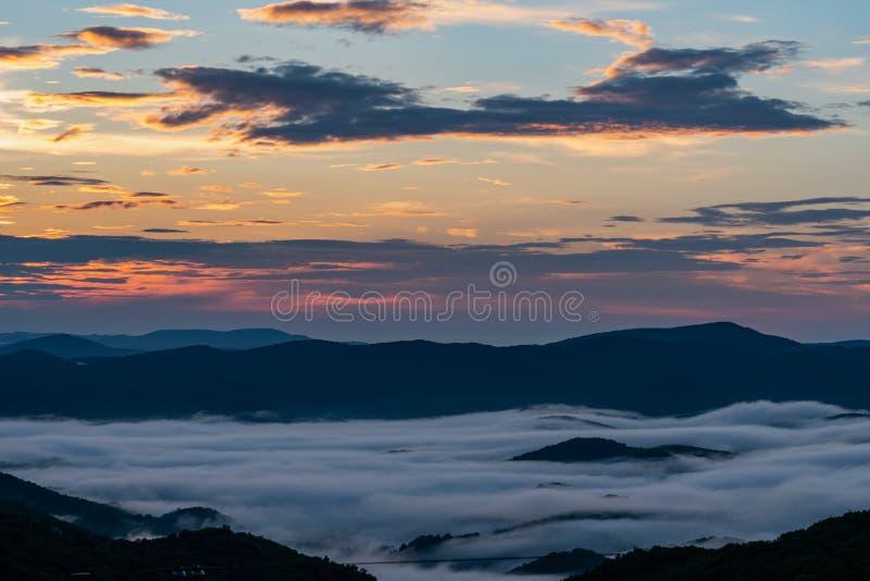 Ανατολή πέρα από την ομιχλώδη μπλε κοιλάδα κορυφογραμμών στοκ εικόνες