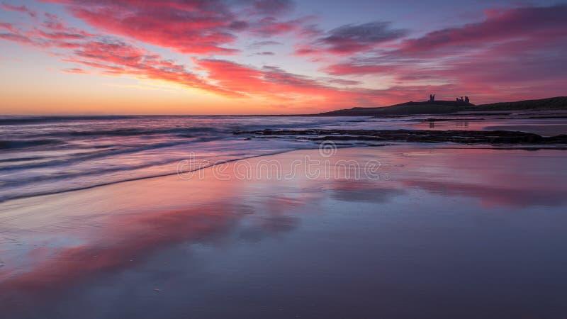 Ανατολή πέρα από Dunstanburgh Castle στην ακτή της Northumberland, Αγγλία, UK στοκ εικόνα με δικαίωμα ελεύθερης χρήσης