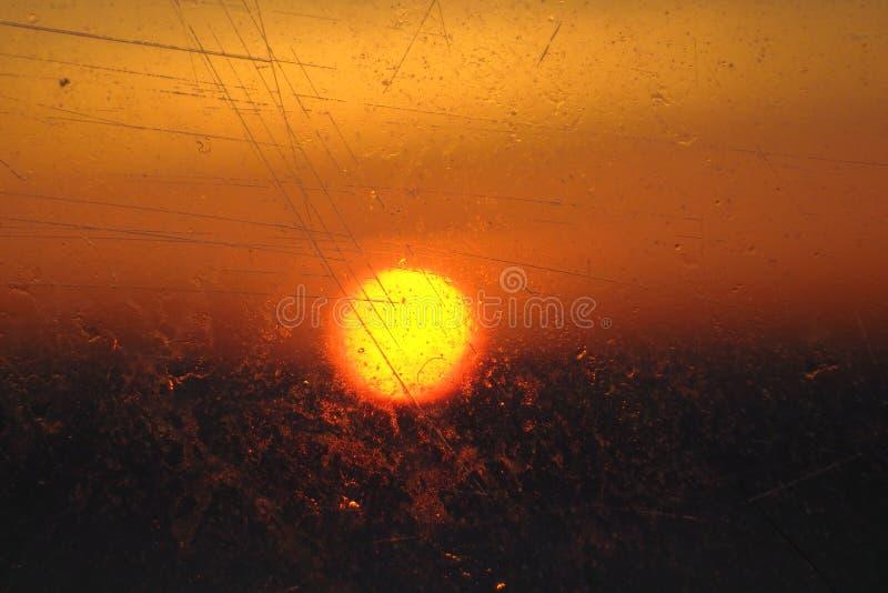 Ανατολή που βλέπει μέσω της γρατσουνισμένης αφηρημένης χρυσής σφαίρας παραθύρων πορθμείων στοκ εικόνες με δικαίωμα ελεύθερης χρήσης