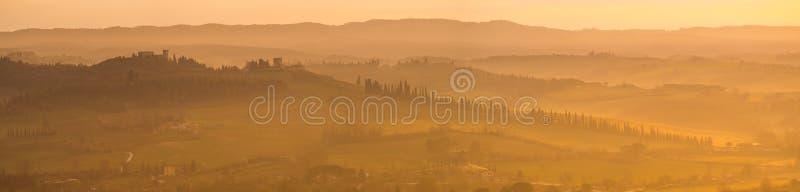 Ανατολή στα εδάφη της Τοσκάνης Θερμά χρώματα στους λόφους και την ελαφριά ομίχλη στοκ εικόνα με δικαίωμα ελεύθερης χρήσης