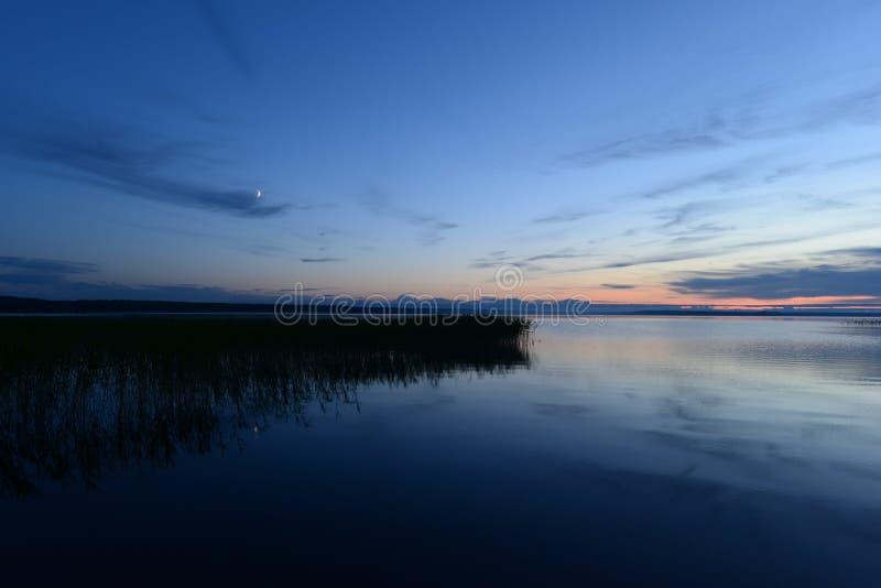 Ανατολή του φεγγαριού στο μπλε ουρανό πριν από το σούρουπο η μέσα σιωπή του νερού λιμνών στοκ φωτογραφίες με δικαίωμα ελεύθερης χρήσης