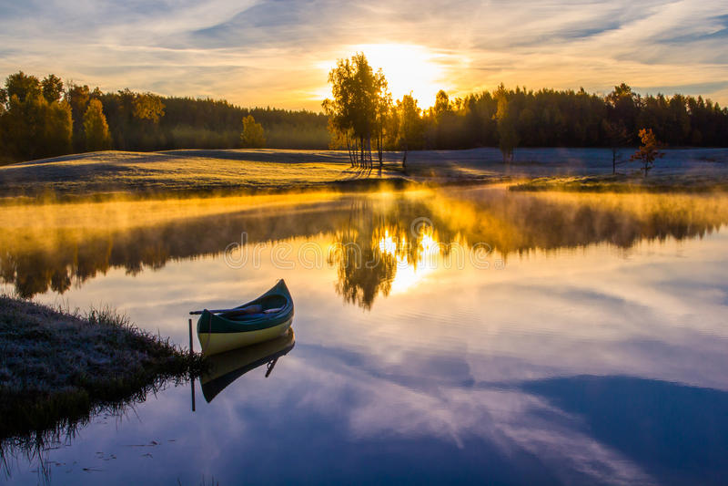 Ανατολή πέρα από τη λίμνη με μια βάρκα στοκ φωτογραφία