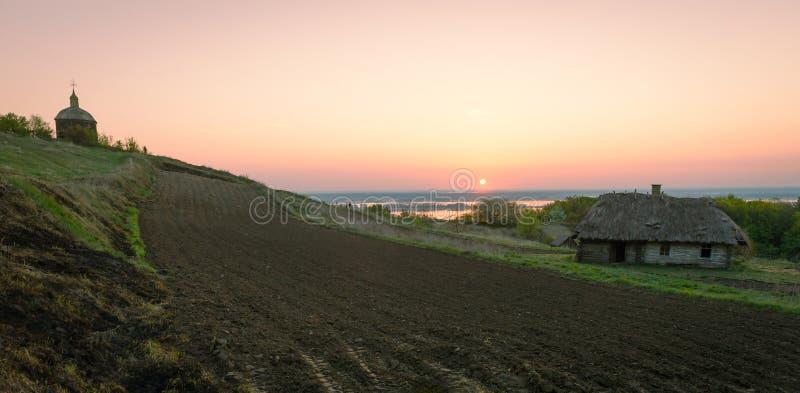 Ανατολή πέρα από τη αγροτική γη με το όργωμα, παλαιό σπίτι, ξύλινο γ στοκ φωτογραφία με δικαίωμα ελεύθερης χρήσης