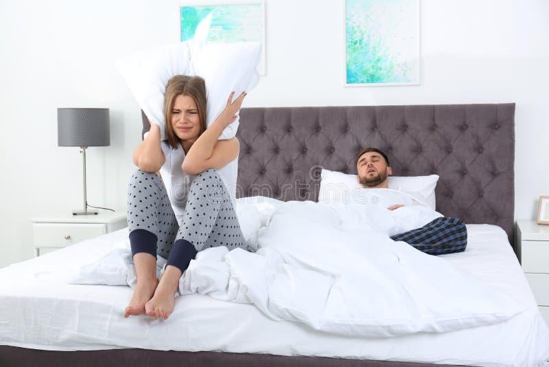 Ανατρέψτε τη νέα γυναίκα καλύπτοντας το κεφάλι της με το μαξιλάρι κοντά στο σύζυγο ύπνου στην κρεβατοκάμαρα στοκ φωτογραφία με δικαίωμα ελεύθερης χρήσης