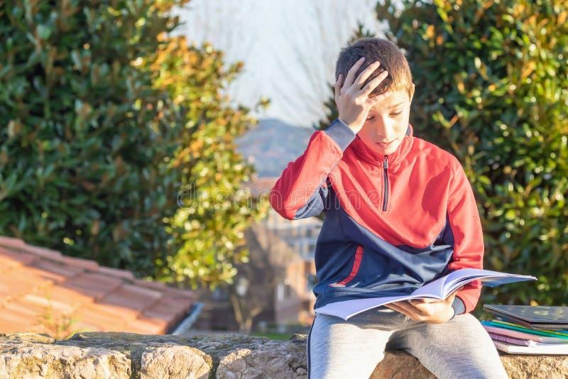 Ανατρέψτε το λυπημένο έφηβο με τα εγχειρίδια και τα σημειωματάρια στοκ φωτογραφία