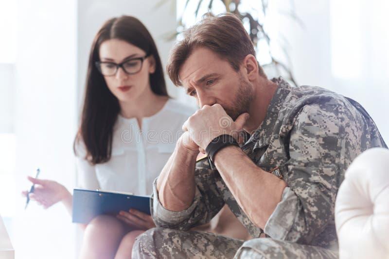 Ανατρέψτε το χιλιετή στρατιώτη που εξετάζει το κενό στο γραφείο ψυχολόγων στοκ εικόνες