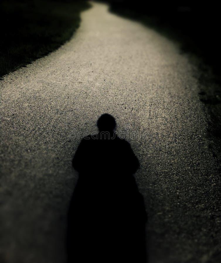 Ανατριχιαστική απόμερη σκιαγραφία στη μακριά άνεμος πορεία στοκ φωτογραφία
